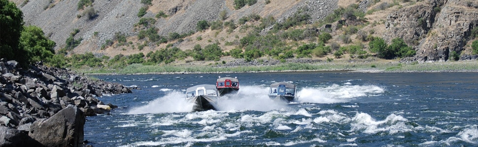 Three Northwest Boats navigating the river rapids